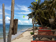 Drewniani kawiarnia stoły na piaskowatym dennym wybrzeżu z drzewkami palmowymi Obraz Stock