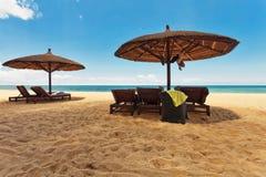 Drewniani krzesła i parasole na białym piasku wyrzucać na brzeg obrazy stock