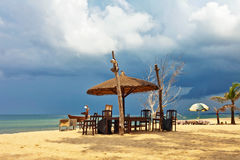 Drewniani krzesła i parasole na białym piasku wyrzucać na brzeg obraz royalty free