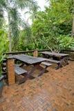 Drewniani krzesła i stołu set przy balkonem w zielonej roślinie uprawiają ogródek Fotografia Royalty Free