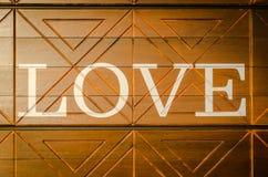 Drewniani listy tworzy słowo KOCHAJĄ piszą na drewnianym tle Fotografia Stock