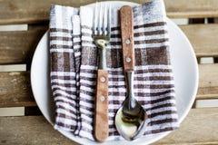 Drewniani naczynia na bielu talerzu z kuchennym ręcznikiem Zdjęcia Royalty Free
