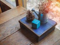 Drewniani przedmioty, Błękitny kubiczny, sosna konusują i suszący kwiat w małej podlewanie puszce na drewnianym stole fotografia royalty free