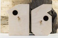 Drewniani ptaków domy w kształtnym liczby na starym nieociosanym drewnianym deski tle Zdjęcie Stock