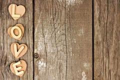 Drewniani serca i list miłosny strona graniczą na nieociosanym drewnie Zdjęcia Royalty Free