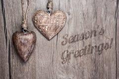 Drewniani serca na rocznika drewnianego tła Sezonowych powitaniach zdjęcie royalty free