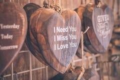 Drewniani serca umieszczający miło na turkusowym rocznika drewna tle Handcrafted drewniani serca z tekstem w pamiątkarskim sklepi Zdjęcia Royalty Free