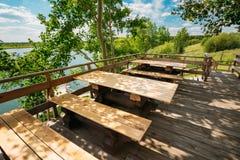 Drewniani stoły I ławki W Plenerowej kawiarni W naturze sunny lato Fotografia Royalty Free