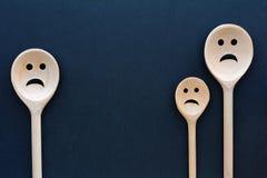 Drewniany łyżki spojrzenie jak smutna rodzina Boleściwe twarze obraz stock