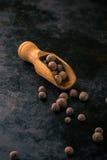 Drewniany łyżkowy pełny allspice na rocznika zmroku tacy zdjęcie royalty free