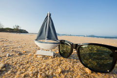 drewniany żagla statku zabawki model i okulary przeciwsłoneczni w dennym piasku Fotografia Royalty Free