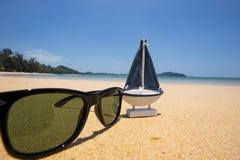 drewniany żagla statku zabawki model i okulary przeciwsłoneczni w dennym piasku Obraz Royalty Free