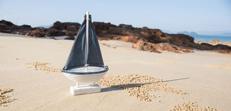 drewniany żagla statku zabawki model w dennym piasku Obrazy Stock