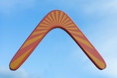 Drewniany australijski bumerang w locie przeciw czystym biel chmurom, niebieskiemu niebu i Obraz Stock