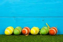 Drewniany błękitny tło z Easter jajkami malował w wibrujących kolorach fotografia royalty free