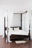 Drewniany baldachimu łóżko i biała kryjówka na podłoga fotografia stock