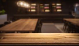 Drewniany bar odpierający przed wygodną zamazaną karczemną restauracją zdjęcia stock