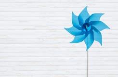 Drewniany biały podławy tło z błękitnym pinwheel lub wiatraczkiem Zdjęcia Stock