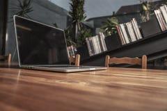 Drewniany biurko w biurze, laptop na nim, boczny widok Zdjęcia Royalty Free