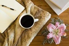 Drewniany biurko z filiżanką kawy, notatnikiem i kwiatem, Fotografia Royalty Free