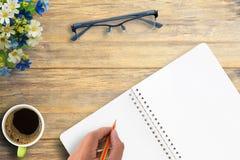 Drewniany biurowego biurka stół z notatnikiem, filiżanką kawy i szkłami, Fotografia Stock