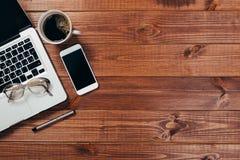 Drewniany biurowego biurka st?? z laptopem, fili?anka kawy i dostawami, fotografia stock