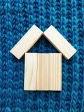 Drewniany bloku dom na błękitnym trykotowym tle fotografia stock
