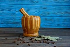 Drewniany brown moździerza pieprz i podpalany liść na stole blisko drewnianej błękit ściany fotografia royalty free
