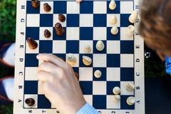 Drewniany chessboard z postaciami na nim ręka robi ruchowi Odgórny widok, zamyka up Edukacja obraz stock