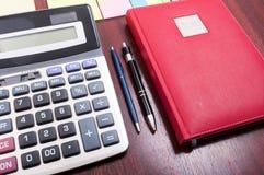 Drewniany desktop z czerwoną agendą i kalkulatorem Zdjęcia Royalty Free