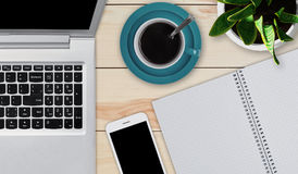 Drewniany desktop z przedmiotami potrzebującymi dla pracy Nowożytny laptop, smartphone, filiżanka kawy i notepad z pustymi prześc zdjęcia stock