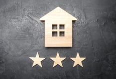 Drewniany dom i trzy gwiazdy na szarym tle Oszacowywać domy i własność prywatna Kupienie i sprzedawanie, wynajmowań mieszkania Fotografia Stock