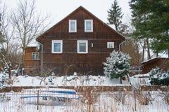 Drewniany dom na zamarzniętym jeziorze z łodzią zdjęcia stock