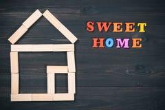 Drewniany dom robić zabawkarscy bloki z cukierki domu inskrypcją na ciemnym drewnianym tle kosmos kopii obrazy royalty free