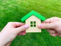 Drewniany dom w ręce młoda rodzina Kupować dom w hipotecznej pożyczce koncepcja real nieruchomo?ci Eco ?yczliwy dom rz?dowy fotografia stock