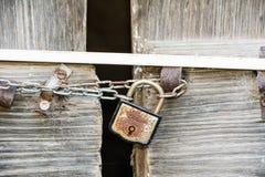 Drewniany drzwi blokował z łańcuchem i ośniedziałą kłódką Fotografia Stock