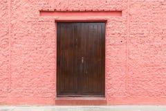 Drewniany drzwi w różowej ścianie Zdjęcie Royalty Free