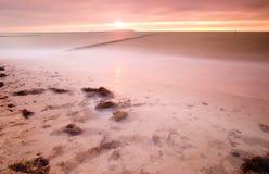 Drewniany falochron na falistym morzu bałtyckim Różowy horyzont z pierwszy gorącymi słońce promieniami Obrazy Stock