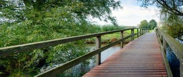 Drewniany footbridge nad małą rzeką w wiejskim krajobrazie Fotografia Royalty Free