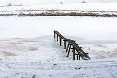 Drewniany footbridge w zamarzniętym śnieżnym stawie w średniogórzach Zdjęcie Stock
