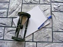 Drewniany hourglass, pióro i agenda na ceglanym tle, Zdjęcia Royalty Free