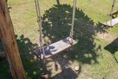 Drewniany huśtawkowy obwieszenie od wielkiego drzewa z światłem słonecznym w ogródzie Obraz Royalty Free
