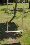 Drewniany huśtawkowy obwieszenie od wielkiego drzewa z światłem słonecznym w ogródzie Fotografia Royalty Free
