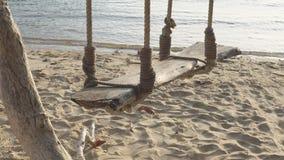 Drewniany huśtawkowy zrozumienie pod drzewnym piaskiem i morze wyrzucać na brzeg zbiory