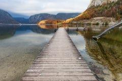 Drewniany Jetty w jeziorze przy Obertraun miastem naprzeciw Hallstatt Au Fotografia Stock