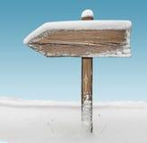 Drewniany kierunku znak z śniegiem na nim z niebem na tle Obraz Royalty Free