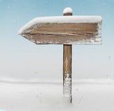 Drewniany kierunku znak z opadem śniegu na tle Zdjęcia Stock