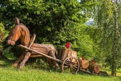 Drewniany koński i fura, dekoracyjny flowerbed w ogródzie Zdjęcie Stock