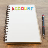 Drewniany kolorowy listowy słowa konto kłaść puszka notatnika z ołówkiem Obraz Stock