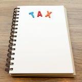 Drewniany kolorowy listowy słowo podatek kłaść puszka notatnika na drewnianym backgrou Obraz Stock